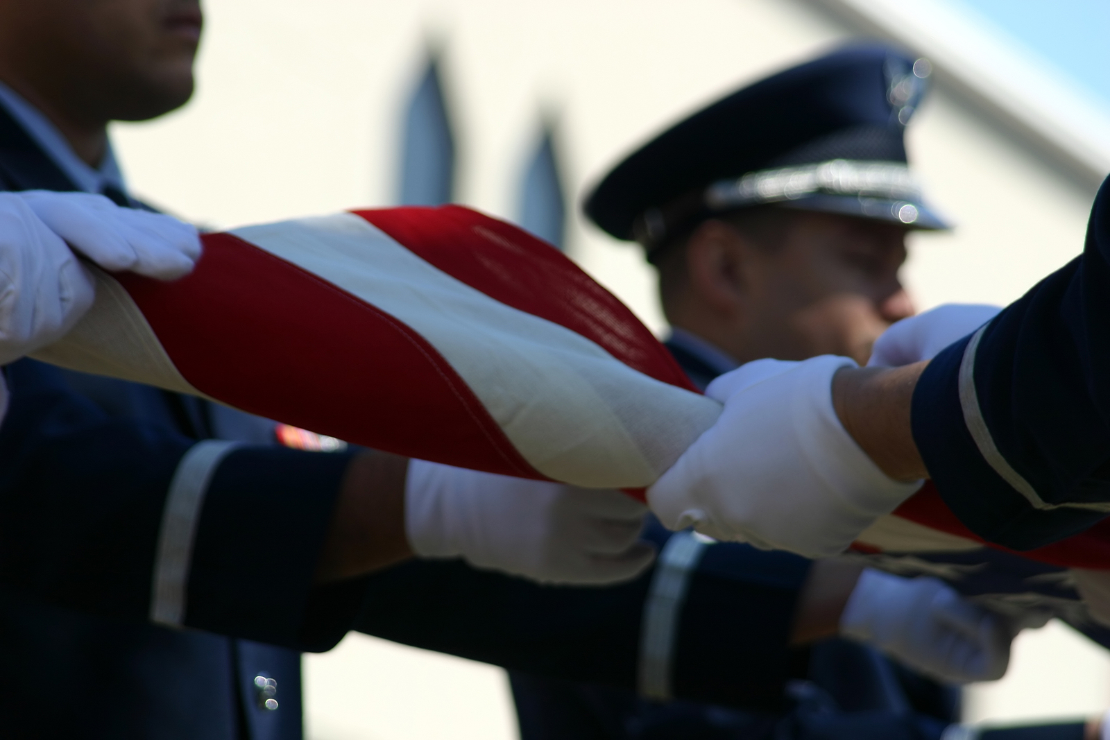 close up view of service members folding a military flag at a military memorial service