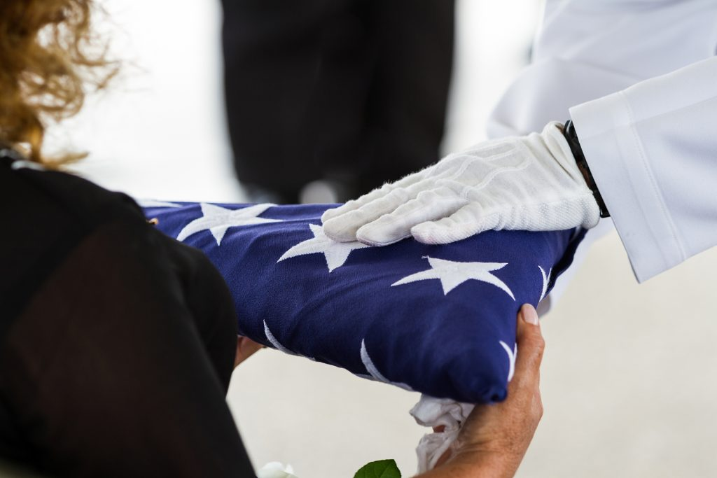 close up view of a folded flag being handed by a military service member to a loved one